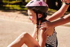 Happy girl sitting on street wearing a bicycle helmet stock image