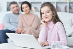 Happy girl  sitting at table with laptop with her parents on bac Royalty Free Stock Image