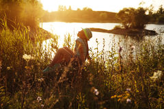 Happy girl sitting under the evening sun Stock Images