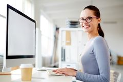 Office girl. Happy girl sitting by workplace with her fingers on keypad and networking in office Royalty Free Stock Photos