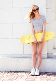 Happy girl with skateboard leaning on the wall Royalty Free Stock Image