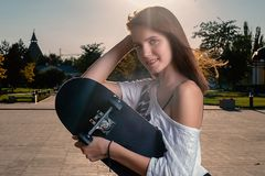 Happy girl with skateboard in summer city backlit stock image