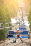Happy girl skier is sitting on ski lift and riding up to the top of the mountain Royalty Free Stock Images
