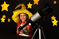 Happy girl in sky watcher costume with a telescope Royalty Free Stock Images