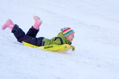 Happy Girl Sledding. Happy young girl sledding in snow in colorful clothing Royalty Free Stock Photo
