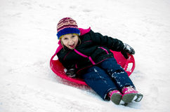 Happy girl sledding down a snowy hill Royalty Free Stock Images