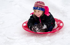 Happy girl sledding with a red saucer sled Royalty Free Stock Photography