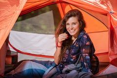 Happy girl in sleeping bag inside tent. Happy young woman in sleeping bag inside tent royalty free stock photos