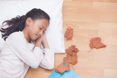 Happy girl sleeping  while lying in the living room with brown d Royalty Free Stock Photo