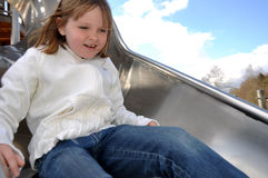 Happy girl on slide Stock Images