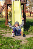 Happy girl on slide in park Royalty Free Stock Photos