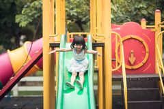 Happy girl on slide playground area. Vintage color stock image