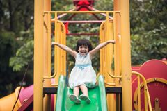 Happy girl on slide playground area. Vintage color stock photography