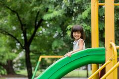 Happy girl on slide playground area. Vintage color royalty free stock images