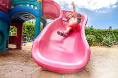 Happy Girl on Slide. On Public Playground royalty free stock photography