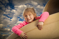Happy girl on the slide. Happy young girl at the park going down the slide stock images