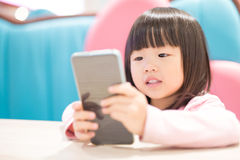Happy girl with smart phone. Child girl happy look smart phone. asian child royalty free stock images