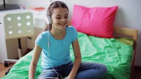 Happy girl with smartphone and headphones at home stock video