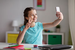 Happy girl with smartphone taking selfie at home Royalty Free Stock Images