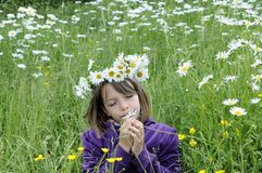 Happy girl smelling and feeling flowers Royalty Free Stock Image