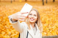 Happy girl with a smile doing selfie in a fall day against. A background of yellow foliage stock photography