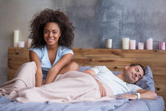 Happy girl smiling while her husband is sleeping Stock Image