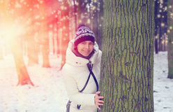 Happy girl smiling and peeking out from behind a tree in the forest on a background of a sunset Royalty Free Stock Images