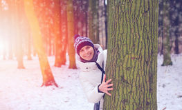Happy girl smiling and peeking out from behind a tree in the forest on a background of a sunset Stock Image
