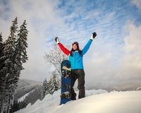 Happy girl snowboarder in snow winter stands on top of mountain Stock Photos