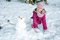 Happy girl and the snowman Royalty Free Stock Photo
