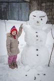 Happy girl and snowman Royalty Free Stock Photo