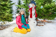 Happy girl with the snowman on a snowy winter walk Stock Photo