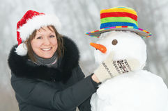 Happy girl and snowman in winter Royalty Free Stock Photo