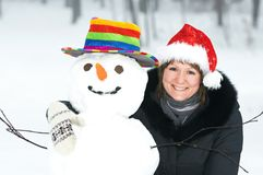 Happy girl and snowman in winter Stock Images