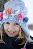 Happy girl in snowy wintry hat Royalty Free Stock Photo