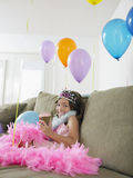 Happy Girl On sofa With Balloons And Cupcake Stock Images