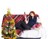 Happy girl on the sofa with a telephone and a gift box Stock Image