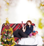 Happy girl on the sofa with a telephone and a gift box Royalty Free Stock Image