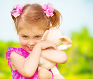 Happy girl with soft toy. Happy smiling girl with lovely soft toy in the garden in daycare, having fun outdoors, spring season, happy childhood concept royalty free stock photography