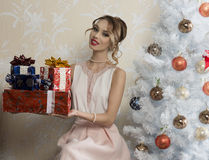 Happy girl with some christmas gifts. Happy female with elegant dress and hair-style sitting near decorated tree in christmas night, smiling and taking some stock photo