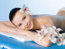 Happy girl in spa salon. Beautiful smiling girl relaxing in beauty spa salon - colored background Stock Photos