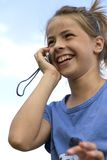 Happy girl while speaking with mobile telephone stock photography