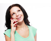 Happy girl speaking. On the phone and looking up; white background Royalty Free Stock Photo