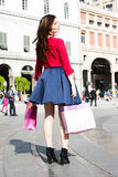 Happy girl spinning in the city with bags. Nicely dressed girl is spinning and having a great time with some colorful bags after a long day of shopping Royalty Free Stock Image