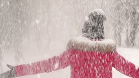 Happy girl spinning under heavy snow in the Park. Young woman enjoying winter day outdoors. Happy girl spinning under heavy snow in the Park. Snow winter dream stock video footage