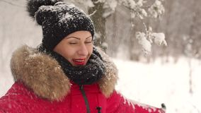 Happy girl is spinning under the heavy snow. Young woman enjoying winter day outdoors. Happy girl spinning under heavy snow in the Park. Snow winter dream. Slow stock footage