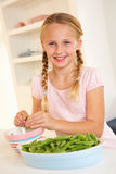 Happy girl splitting peas in kitchen Royalty Free Stock Photography