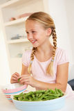Happy girl splitting peas in kitchen Stock Image