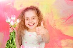 Happy girl with spring tulip flowers, womens, mothers day holiday. Happy easter egg. holiday bunny and eggs, spring flower backround small child smiling face Royalty Free Stock Photo
