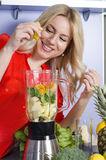 Happy girl squeezing lemon into juicer Stock Images
